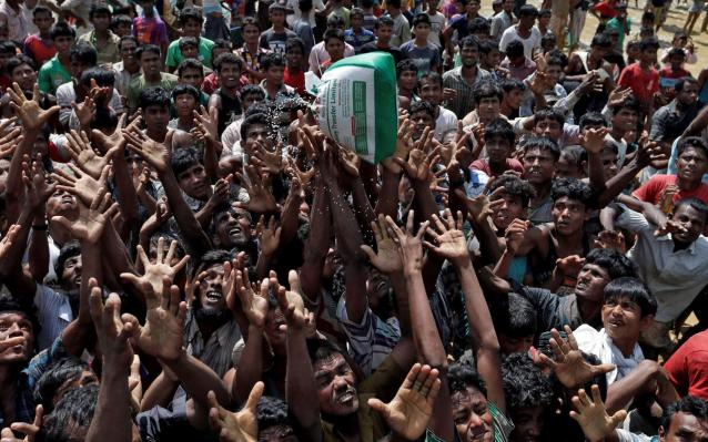 Rohingya refugees react as aid is distributed in Cox's Bazar